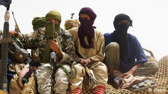 Fighters from Islamist group Ansar Dine stand guard during the handover of a Swiss female hostage for transport by helicopter to neighboring Burkina Faso,