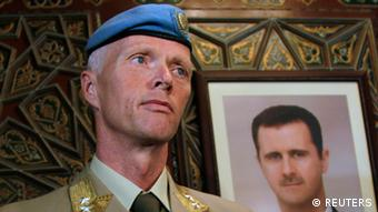 The Chief of the U.N. Supervision Mission to Syria, Norwegian Major General Robert Mood looks on during his arrival to Damascus airport, April 29, 2012. The photo at the back of the wall is of Syrian President Bashar al-Assad.