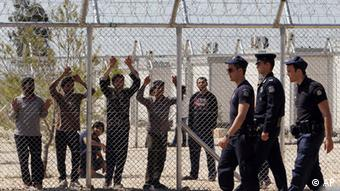 Illegal immigrants watch from behind a fence as police patrol the perimeter of a detention center at Amygdaleza, on the northern fringes of Athens, Monday, April 30, 2012
