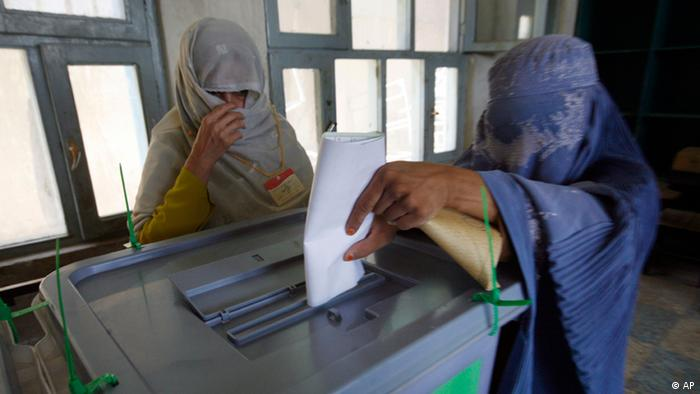 An Afghan woman, right, casts her vote in the presidential election at a polling station in Kandahar province, south of Kabul, Afghanistan, Thursday, Aug. 20, 2009. (AP Photo/Musadeq Sadeq)