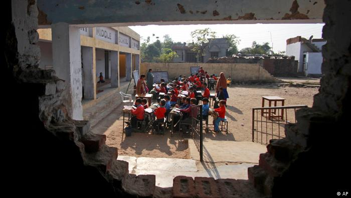 Indian school children attending a class are seen through a damaged wall at a government school in the outskirts of Jammu, India, Thursday, Dec.2, 2010.Indian technology mogul Azim Premji has announced he will donate nearly $2 billion to fund education and development programs in India's villages in one of the largest charitable donations in the country's history.(ddp images/AP Photo/Channi Anand)