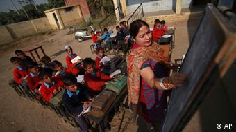 Indian school children attend a class in the open at a government school (ddp images/AP Photo/Channi Anand).