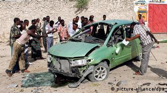 epa03202800 People gather around a car that exploded near KM4 junction in Mogadishu, Somalia, 01 May 2012. A car carrying explosives went off in central Mogadishu, killing at least three. A separate suicide attack targeted a cafe in the town of Dhusomareb, some 600km north of Mogadishu, killed at least two lawmakers and three civilians, reports say. Although no group has claimed responsibility, most of the suicide attacks in Somalia are reportedly Atentado em Mogadíscio, a capital da Somália, pertrado pela milícia Al-Shebab, em maio de 2012