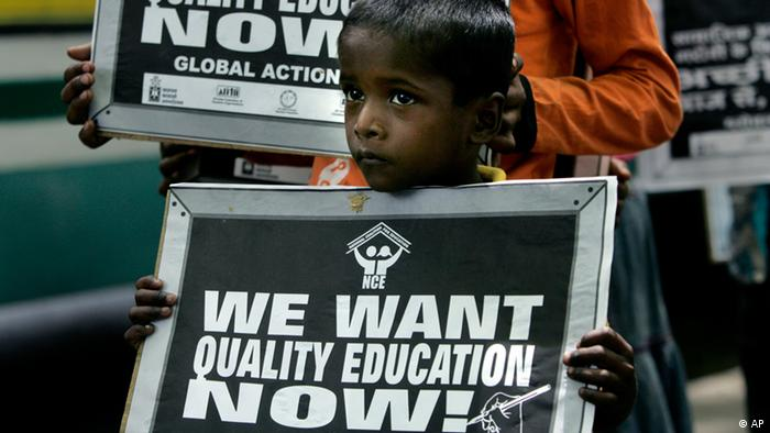 An underprivileged boy holds a banner during a rally saying We want quality education now in India