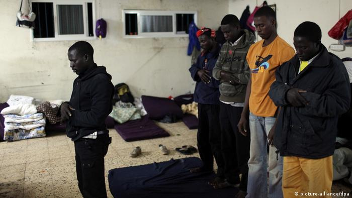 African refugees pray at a shelter in Tel Aviv, Israel,