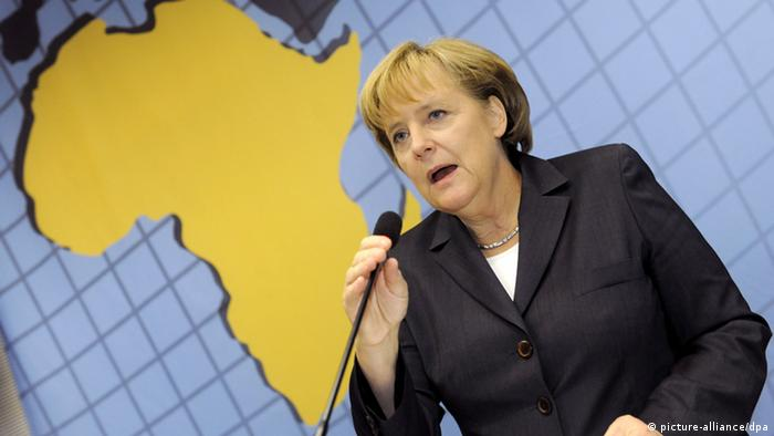 Chancellor Merkel is speaking in front of a large map of Africa.