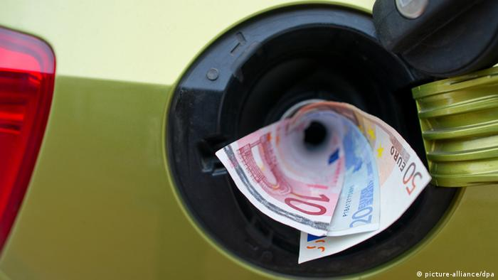 Euro banknotes disappearing in a car tank