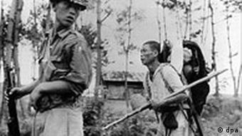 Ein geflüchteter nordkoreanischer Bauer wird Anfang August 1950 hinter die Kampflinie geführt
