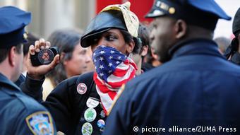Zwei Polisisten und ein Mann mit Kamera und US-Fahne vor dem Mund