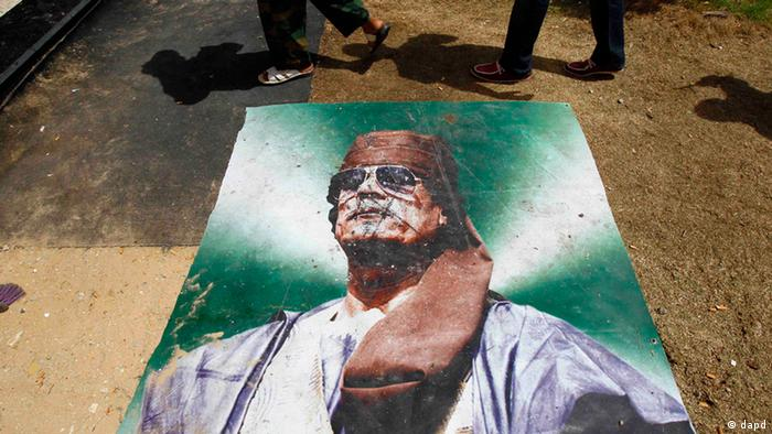 A group of people of Somali origin who are suspected of being mercenaries for Moammar Gadhafi walk past a poster of him as they are held in the Tripoli Oil institute building by the Libyan rebel Zentan Al Kakaa Brigade inTripoli, Libya, Sunday, Sept. 4, 2011 prior to being released to the custody of the UNHCR refugee agency. (Foto:Francois Mori/AP/dapd)