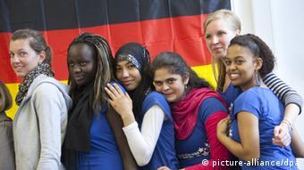 Учащиеся одной из школ во Франкфурте-на-Майне на фоне немецкого флага