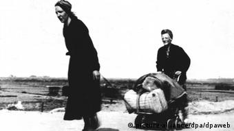 Two women walking across the land with a hand trolley during the Dutch Hunger Winter in April 1945
