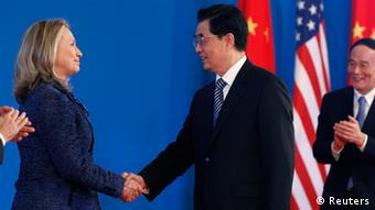 China's President Hu Jintao (R) shakes hands with U.S. Secretary of State Hillary Clinton, Reuters