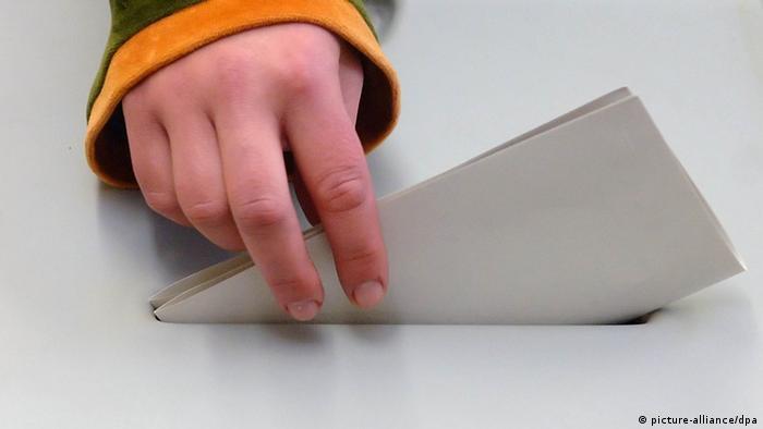 Рука, опускающая бюллетень в урну