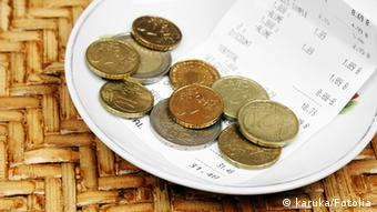 Coins and a restaurant bill on a small plate
