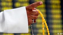 A Bahraini trader holding his prayer beads gestures in front of the trading board Monday, Oct. 13, 2008, at the Bahrain Stock Exchange in Manama, Bahrain. Many businessmen in the Persian Gulf island nation, an offshore and Islamic banking hub, are nervous about fallout from the U.S. financial collapse despite government reassurances Bahrain's growing economy should be secure. (ddp images/AP Photo/Hasan Jamali)