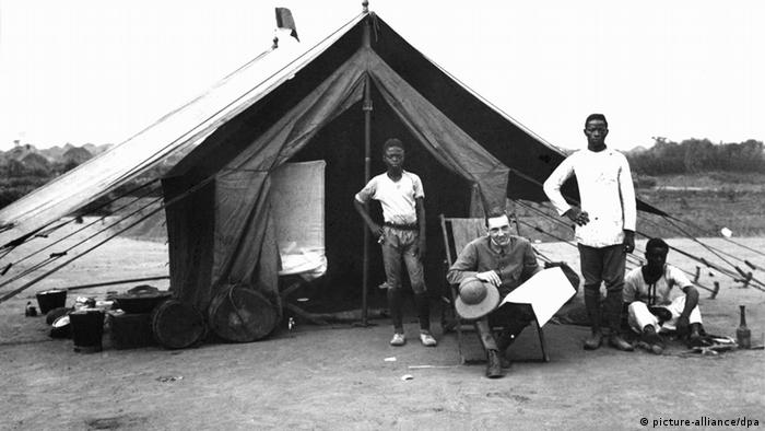 Three people in front of a tent