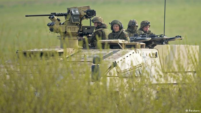 German soldiers sit on a armoured fighting vehicle Boxer during a presentation of German army Bundeswehr in Putlos, northern Germany on April 25, 2012.