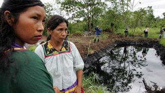 Cofan indigenous women stand near a pool of oil in Ecuador's Amazonian region