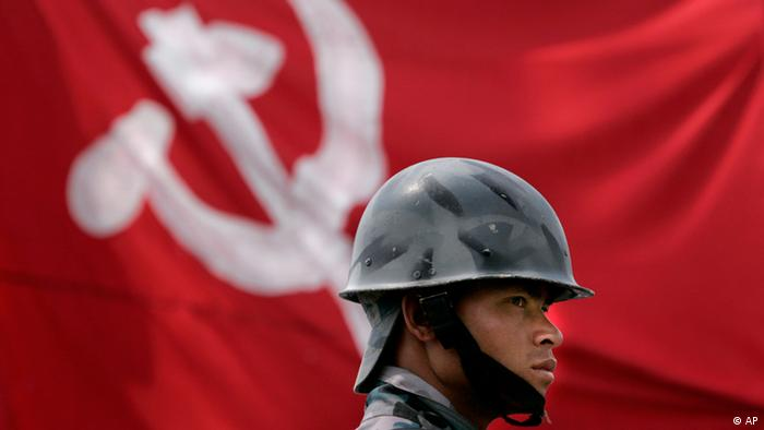 A Nepali policeman stands guard against the flag of the Communist party of Nepal (Maoist) outside a vote counting center, in Katmandu, Nepal, Saturday, April 12, 2008 (AP Photo/Manish Swarup)