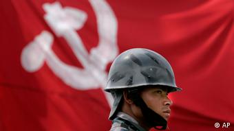 A Nepali policeman stands guard against the flag of the Communist party of Nepal (Maoist)