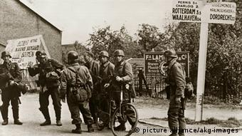 Paratroopers with motorbike at road junction, with signposts