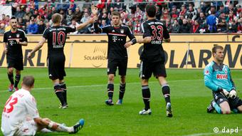 Munich's Thomas Mueller, center, celebrates his team's opening goal as Cologne's goal keeper Michael Rensing, right, looks on during the German first division Bundesliga soccer match between 1. FC Cologne and Bayern Munich in Cologne, Saturday, May 5, 2012. (Foto:Michael Probst/AP/dapd) NO MOBILE USE UNTIL 2 HOURS AFTER THE MATCH, WEBSITE USERS ARE OBLIGED TO COMPLY WITH DFL-RESTRICTIONS, SEE INSTRUCTIONS FOR DETAILS