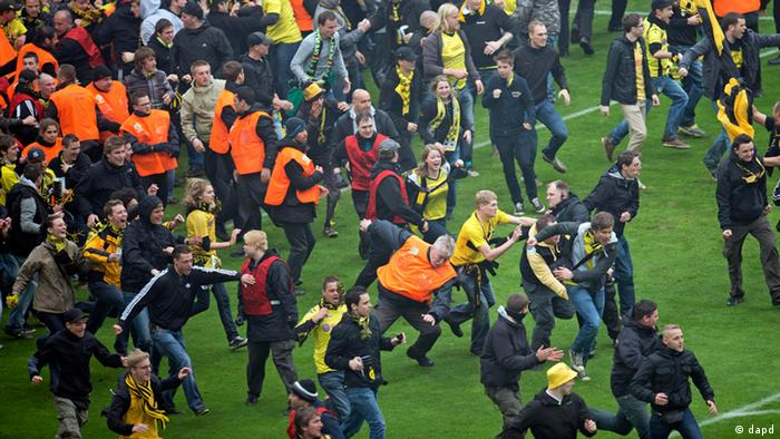 Dortmund's supporters enter the pitch after the German first division Bundesliga soccer match between Borussia Dortmund and SC Freiburg in Dortmund, Germany, Saturday, May 5, 2012. Borussia Dortmund defended the title of last year and is German Bundesliga Champion 2012 again. (Foto:Martin Meissner/AP/dapd) - NO MOBILE USE UNTIL 2 HOURS AFTER THE MATCH, WEBSITE USERS ARE OBLIGED TO COMPLY WITH DFL-RESTRICTIONS, SEE INSTRUCTIONS FOR DETAILS -
