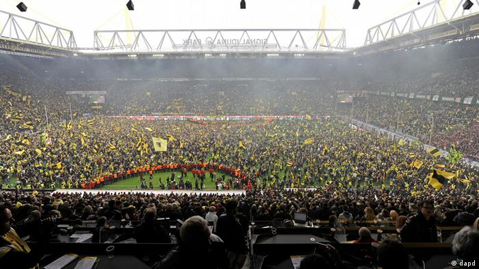 Dortmund's supporters have entered the pitch after the last German first division Bundesliga soccer match between Borussia Dortmund and SC Freiburg