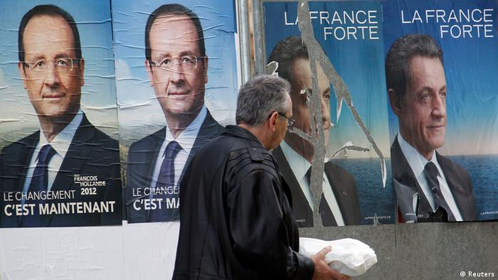 A man walks past official campaign posters for Francois Hollande and Nicolas Sarkozy
