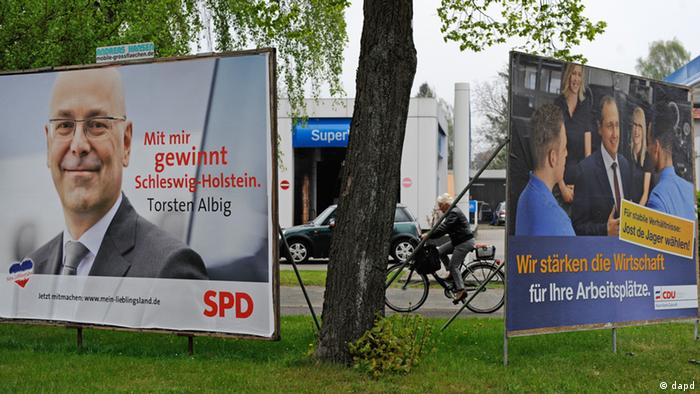 A cyclist passes campaign billboards for CDU and SPD