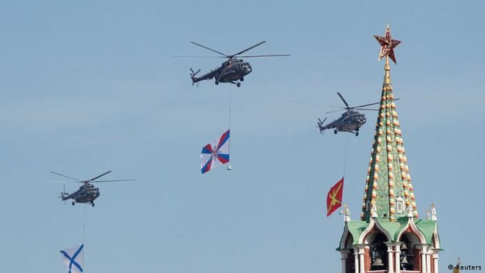 Russian helicopters carrying military insignias fly near the Kremlin