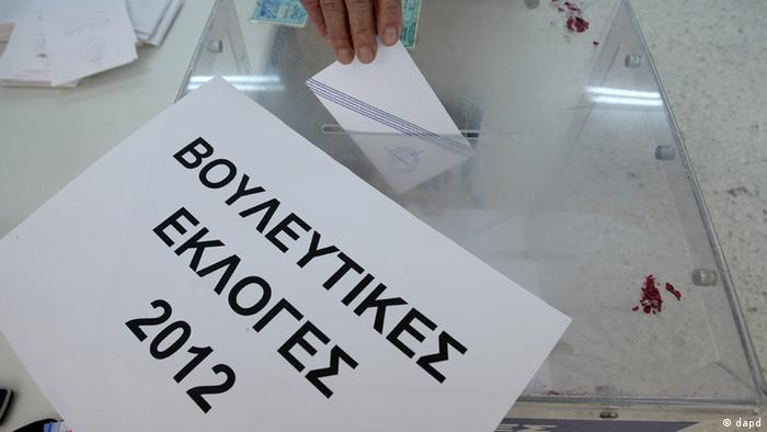 An elderly man casts his ballot as a sign reads ''Parliamentary Elections 2012'' at a polling station in Athens, Sunday, May 6, 2012. Greeks are voting today in elections critical to getting international bailout support as angry voters appear more than ready to punish both major parties for the country's decimated economy. (Foto:Thanassis Stavrakis/AP/dapd)