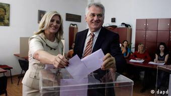 Close-up of Nikolic, right, and his wife Dragica putting their ballot papers into a transparent box