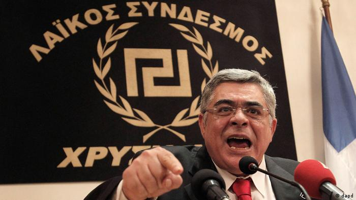 Golden Dawn leader Nikolaos Michaloliakos speaks during a news conference in front of a banner with the twisting Maeander, an ancient Greek decorative motif that the party has adopted as its symbol in Athens, Sunday, May 6, 2012. The far-right Golden Dawn party is set to win as much as 8 percent of the vote, according to exit polls, as Greeks punished traditionally dominant parties that backed harsh austerity measures tied to debt relief agreements. (Foto:Petros Giannakouris/AP/dapd)