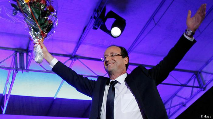 President-elect Francois Hollande holds a bouquet of roses after delivering his speech in Tulle