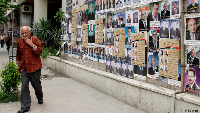 A man walks past posters of parliamentary candidates on a street in Damascus