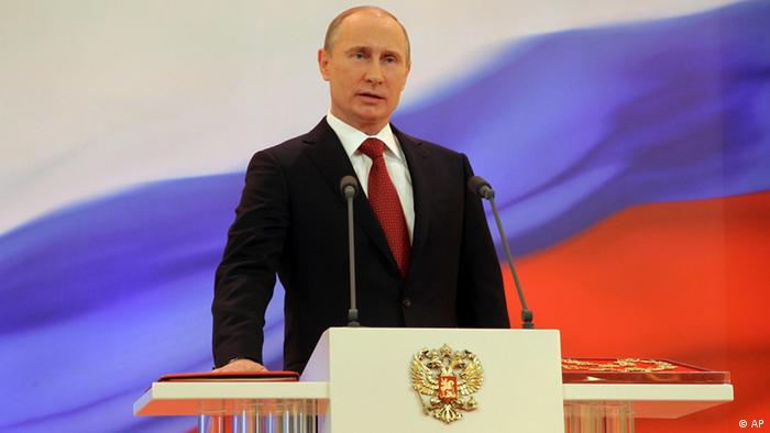 Vladimir Putin speaks with his hand on the Constitution during his inauguration ceremony