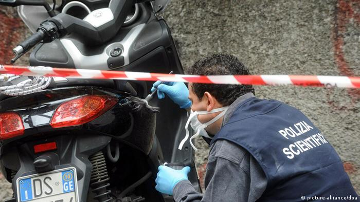 Italian Scientific Police officer examines motorbike probably used for attack