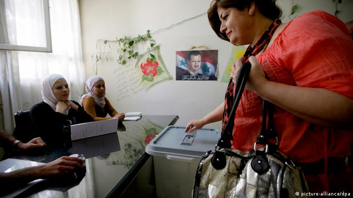 epa03209442 A Syrian woman casts her ballot for parliamentary elections at a polling station in Kafarsouseh area in Damascus, Syria, 07 May 2012. Syrians started voting to choose a new parliament amid a total boycott by the opposition and continued violence that killed at least 11 people. The election initially scheduled for September was postponed due to the uprising against President Bashar al-Assad. A total of 7,195 candidates including 710 women registered to contest the 250 seats, according to state news agency SANA. EPA/NABIL MOUNZER