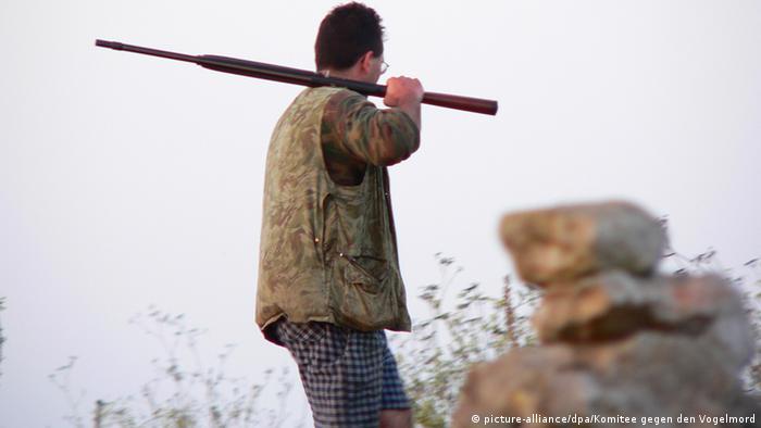 Ein Jäger läuft auf Malta mit einem Gewehr über der Schulter über eine Wiese. (Copyright: Foto: Komitee gegen den Vogelmord)