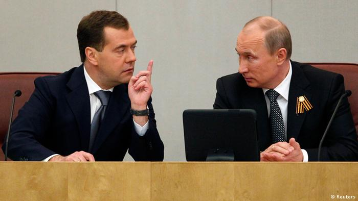 Russia's President Vladimir Putin (R) speaks with former President and prime ministerial candidate Dmitry Medvedev at a session of the Russian State Duma in Moscow May 8, 2012. Putin asked Russia's lower house on Tuesday to confirm his ally Medvedev as prime minister in a job swap that has angered many Russians and sparked protests against the men's grip on power. REUTERS/Maxim Shemetov (RUSSIA - Tags: POLITICS)