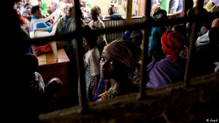A Congolese refugee sits with others at the Nkamira transit centre for refugees in western Rwanda