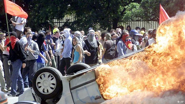 Burning car and protesters (AP)