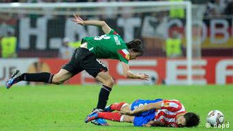 Athletic Bilbao's Iturraspe tackles Atletico Madrid player, Diego in the Europa League final.