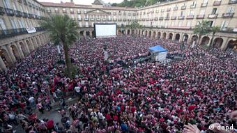 In Madrid, football fans watch the Europa League final on the big screen in a public square.