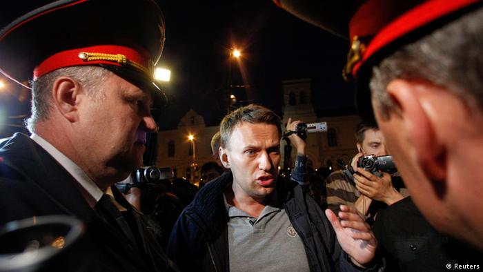 Prominent anti-corruption blogger Alexey Navalny talks to police officers during a rally