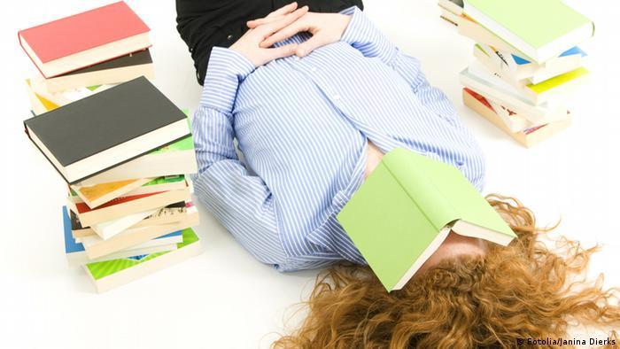 Frau liegt auf Boden mit Buch über dem Gesicht (Foto: Fotolia)