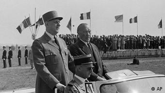 French President Charles De Gaulle and his guest, West Germany's Chancellor Konhad Adenauer, stand upright in their car to review a parade of French and German troops at the Mourmelon training grounds near Reims, France, July 8, 1962. Adenauer currently is in France on an official visit. The two also visited nearby Reims Cathedral. (ddp images/AP Photo)