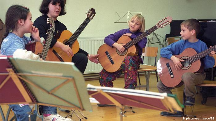 School children learn guitar